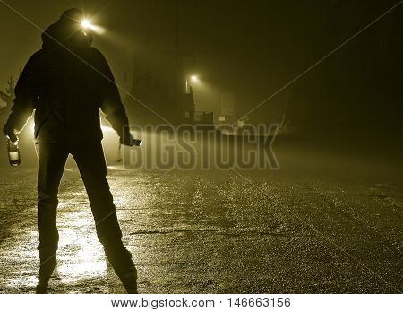Drunk man silhouette standing in road on foggy night car headlights approaching bottle in hand