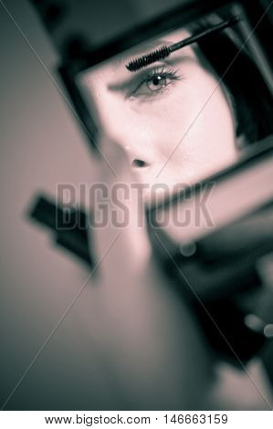 Image of woman reflected in the mirror when putting on mascara.