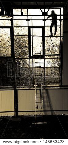 Construction worker climbing on scaffolding. Image is sepia toned figure of the construction worker is silhoutted.