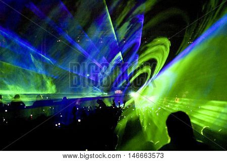 Crowd of people and laser show at rave party
