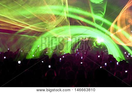 Crowd dancing and laser show in a club. Clubbing fun rave party show