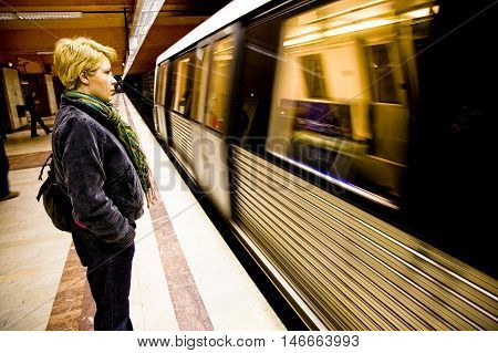 A view of a woman standing on a train or subway platform as a train rushes by.
