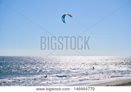 Malibu, California, USA - September 2016: Kitesurfing people ride on the waves