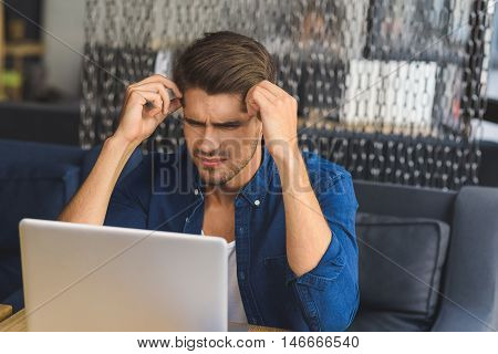 it is impossible, man sitting in front of laptop with befuddled look