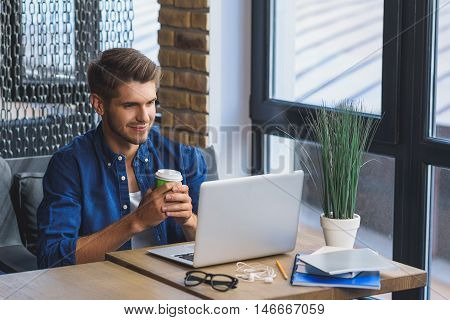 on my way to success, satisfied guy sitting in front of laptop with cup of coffee