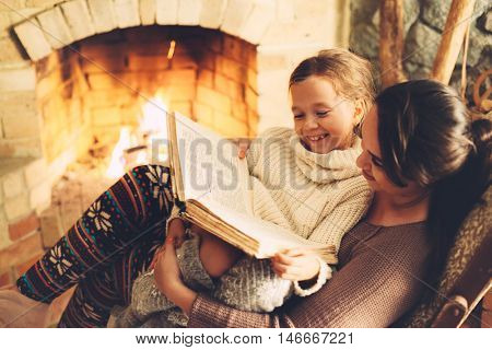 poster of Mom with child reading book and relaxing by the fire place some cold evening, winter weekends, cozy