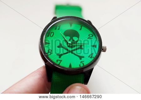 Skull and bones on a dial of unnamed hand watch. Time running fast and killing sometimes.