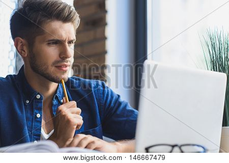 in front of a laptop designer thinking how to solve a problem