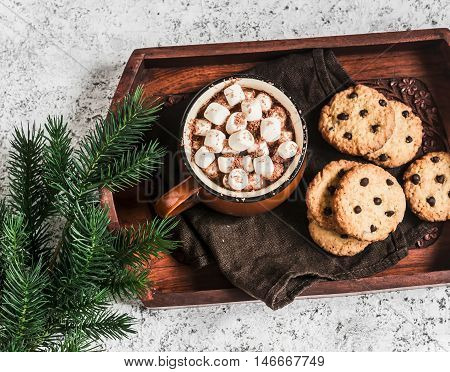 Hot chocolate with marshmallows and chocolate chips oatmeal cookies on wooden tray on a bright background