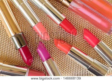 Collection of lipsticks on golden woman pursue background