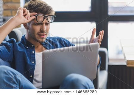 confused worker looking into laptop while working at home
