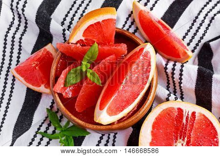 Juicy grapefruit Pilled pieces in wooden bowl with fresh mint lieves and slices