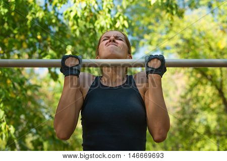 Pull ups by female on pull up bar in metropark, color image