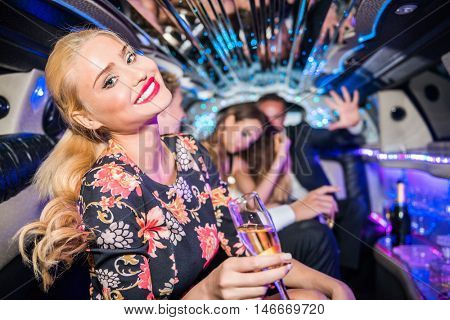Smiling Young Woman Holding Champagne Flute In Limo