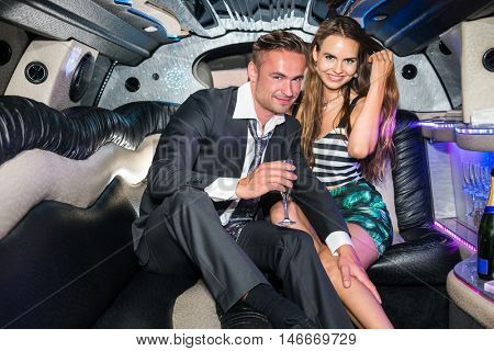 Happy Glamorous Couple With Champagne Flute In Limousine