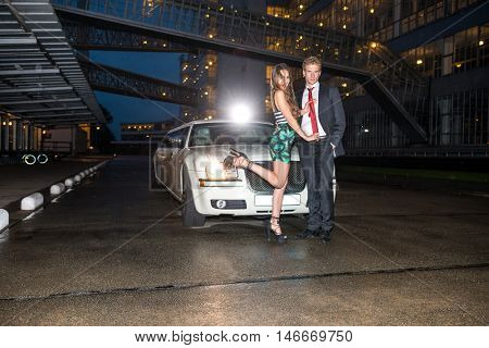 Glamorous Couple Standing In Front Of Limousine On Street