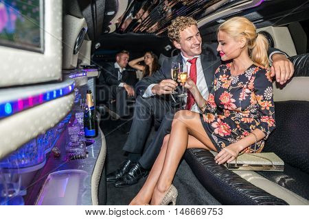 Couple Toasting Champagne Flutes In Limousine