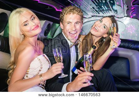 Excited Man With Women Enjoying Champagne In Limousine