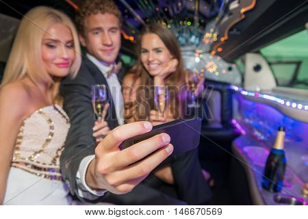 Young Man With Friends Taking Selfie In Limousine