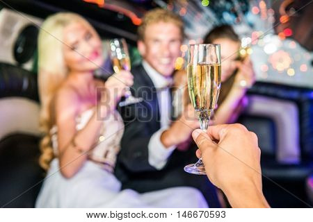 Hand Toasting Champagne Flute With Friends In Limousine