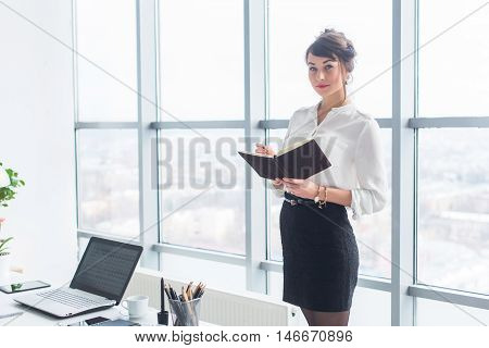 Beautiful female clerk standing in office at her workplace, holding planner, reading timetable for the day, side view portrait