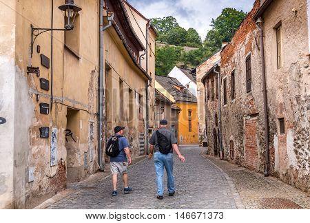 Two friends walking through back street in the town of Cesky Krumlov Czech Republic