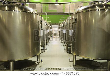 Rows of metal tanks for the fermentation of beer. A small brewery.