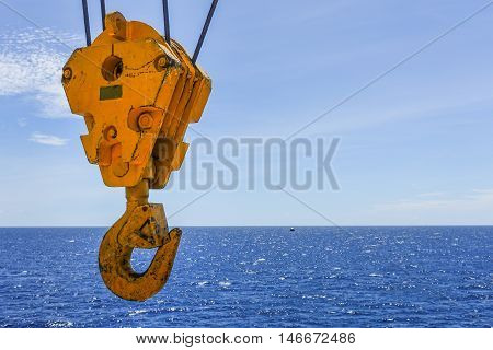 Crane hook in the sea with sky and clouds background on offshore platform.