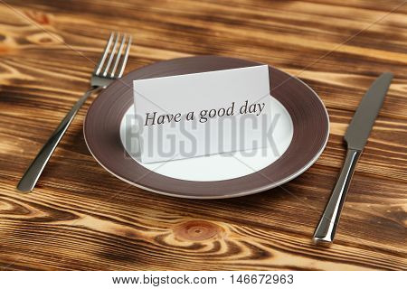 Brown plate on a brown wooden table, have a good day
