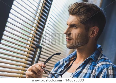 rest is almost over, freelancer took off his glasses and concentrating in front of a window