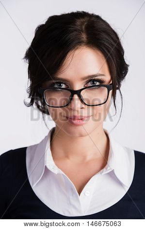 Attractive businesswoman peering over her glasses, white background.
