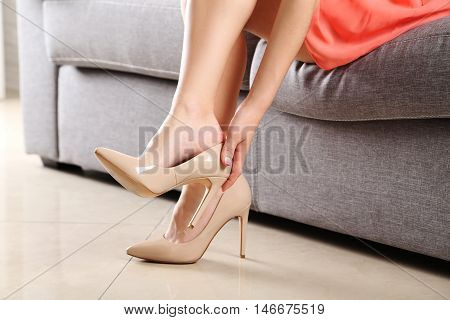 Female Legs With Beige High Heels On Grey Sofa