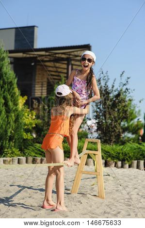 Two girls having fun on sling. Girl teenagers learn to walk on a tightrope with his girlfriend.