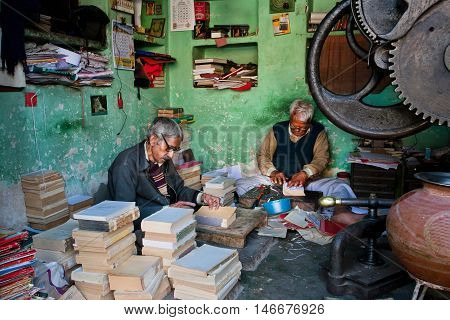 AJMER, INDIA - FEB 11, 2015: Workplace of two seniors repairing antique books on February11 2015. Ajmer is a manufacturing trade centre with population 552000 people