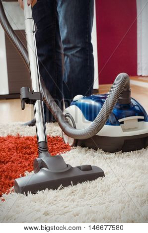 Man Vacuums Shaggy Carpet In The Apartment.