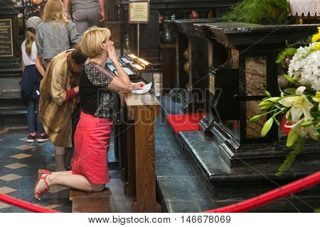 POLAND, KRAKOW - MAY 27, 2016: Prayers in the medieval St Mary's church in Krakow. St. Mary's Church was built in the XIII-XIV century.