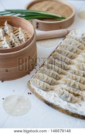 Raw Homemade Chinese Dumplings on Wooden Board.