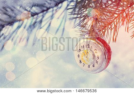 New Year winter background -New Year glass Christmas toy in the form of clock covered with winter snow and showing the New Year Eve on snowy winter fir tree branch. New Year winter card. Christmas and New Year winter background. Shallow DOF. Winter festiv