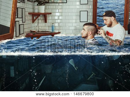 Young man having hair dress in flooded barbershop, barber working with hair clipper