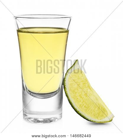 Shot of gold tequila with lime slice isolated on white
