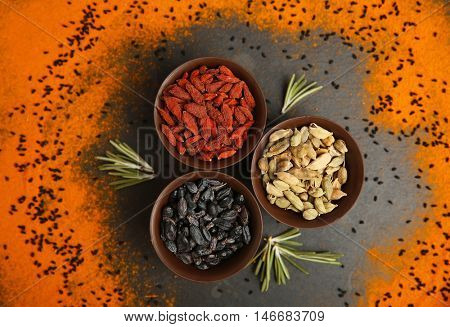 Dried spices in bowls on color background