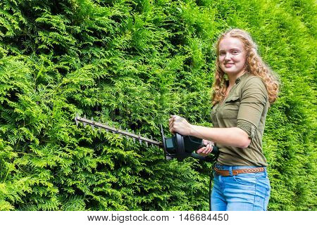 Young caucasian woman holding hedge trimmer at green conifers