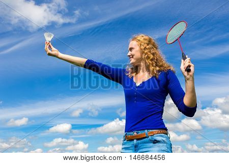 Young caucasian woman holding shuttle and badminton racket against blue sky with white clouds