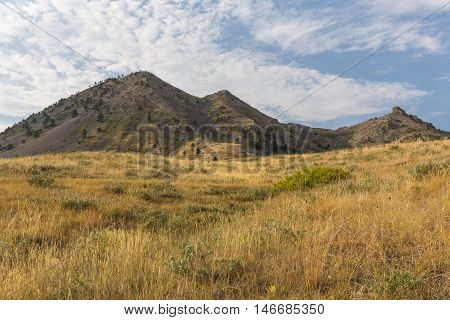 A scenic butte with a foreground grassy field.