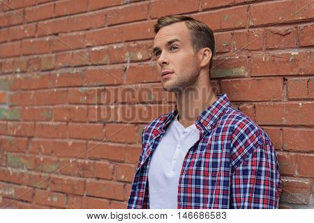I love this city. Cropped shot of handsome young man looking away thoughtfully in front of brick wall