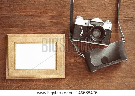 Vintage camera and frame on wooden background