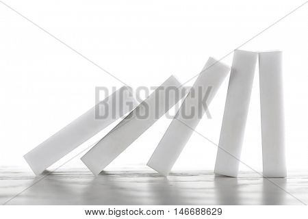 Line of dominoes falling on light wooden background