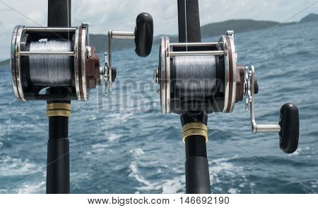 Fishing rods on a boat over blue sea and sky. Picture of two fishing rods in pole holders on the back of a boat