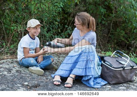 Grandmother to her grandson pours tea from a thermos relaxing in the park