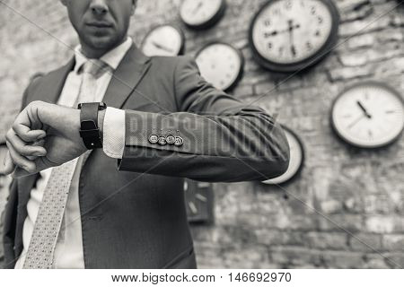 Keeping the time just got hi tech. Black-white shot of young man wearing in suit and tie, checking time on smartwatch